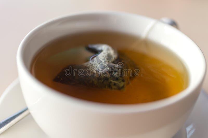 Tasse de mug blanche à tisane verte avec un teabag à l'intérieur refermez images libres de droits