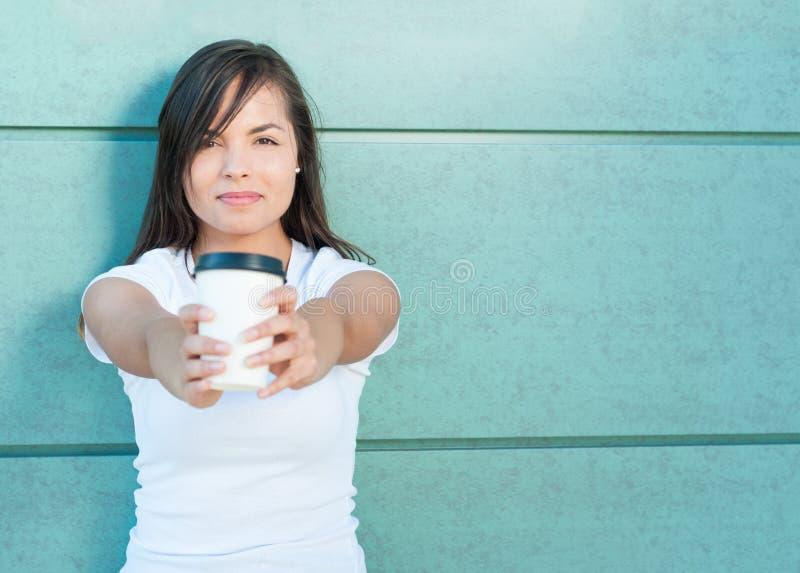 Tasse de offre de sourire de fille attirante de café à emporter photographie stock libre de droits