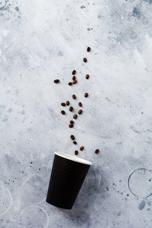 Tasse de papier noire avec les grains de café et les tubules dispersés sur le vieux fond concret gris photos stock