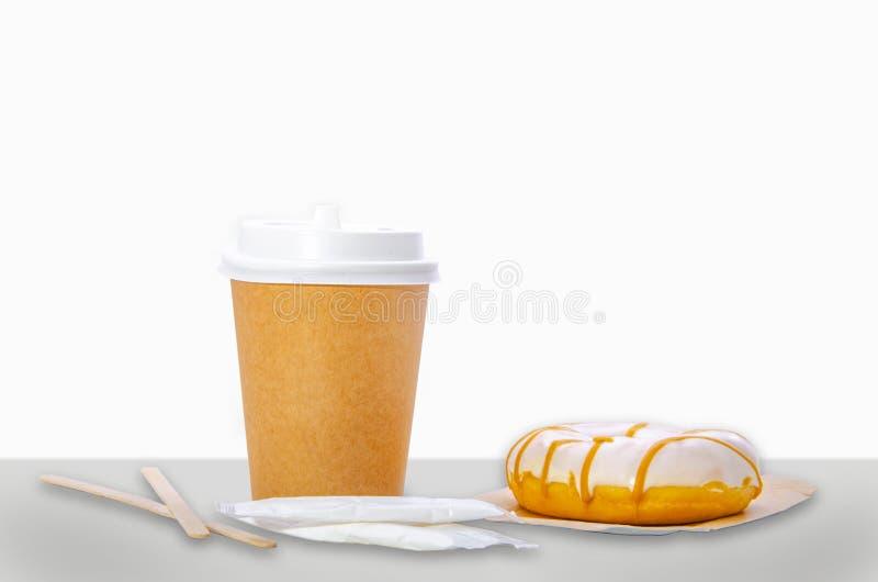 Tasse de papier pour le café, les bâtons en bois, le sucre dans les sacs et le beignet Fond blanc photographie stock