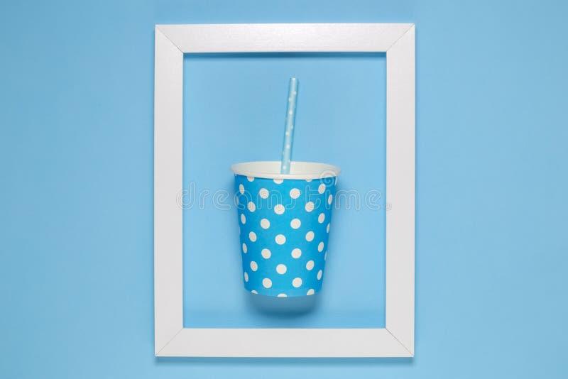 Tasse de papier rose simple avec la paille à boire encadrée sur le papier peint bleu simple photographie stock