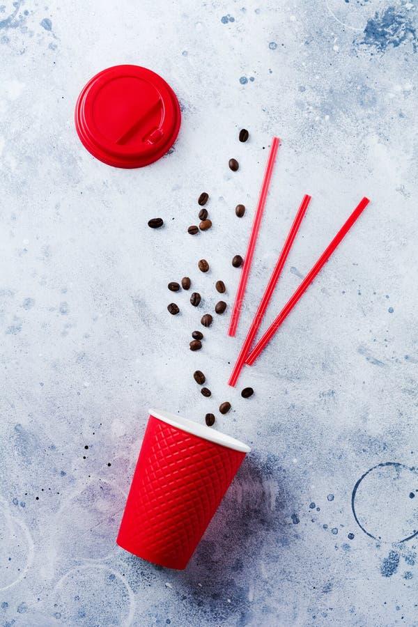 Tasse de papier rouge avec les grains de café et les tubules dispersés sur le vieux fond concret gris photo stock