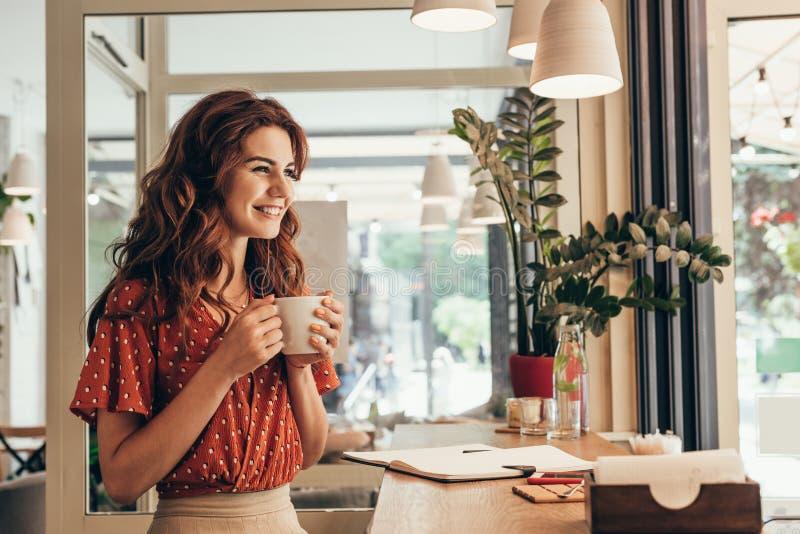 tasse de participation de jeune femme de café de sourire à la table avec le carnet photo stock