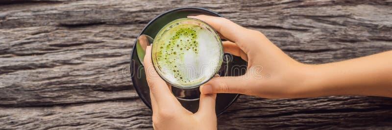Tasse de participation de la main des femmes de Latte de matcha, thé vert, sur la vieille BANNIÈRE en bois de table de fond, LONG image libre de droits