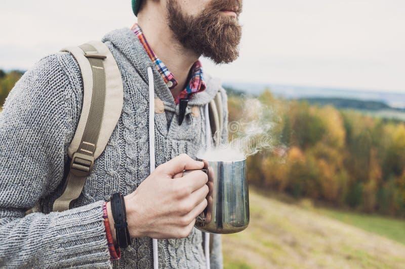 Tasse de participation de voyageur de jeune homme avec la boisson chaude voyage et concept actif de mode de vie photo stock