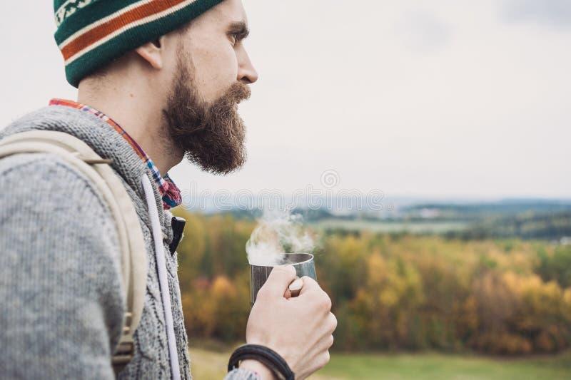 Tasse de participation de voyageur de jeune homme avec la boisson chaude voyage et concept actif de mode de vie photographie stock libre de droits