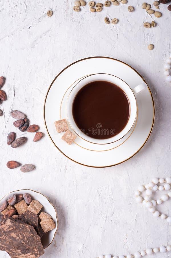 Tasse de porcelaine de café de mocca avec du chocolat naturel, des haricots de cocao, des haricots verts de coffe et des perles d photographie stock libre de droits