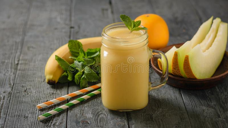 Tasse de smoothie de melon avec les feuilles en bon état, les tranches de melon et les tubes de cocktail sur une table en bois photographie stock