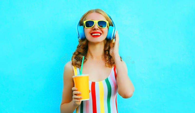 Tasse de sourire heureuse de participation de femme de jus écoutant la musique dans des écouteurs sans fil sur le bleu coloré images stock