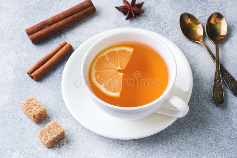Tasse de thé avec le citron et le sucre roux, la cannelle et l'anis sur la table image libre de droits