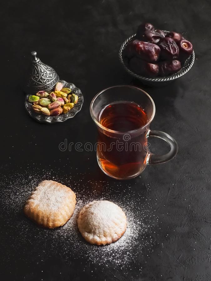 """Tasse de thé avec les biscuits égyptiens """"EL Eid de Kahk """"et les dates sur la table noire image stock"""