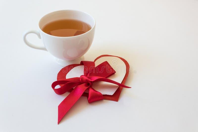 Tasse de thé blanche avec des coeurs de valentine de thé et de papier attachés avec le grand ruban rouge de satin photo stock