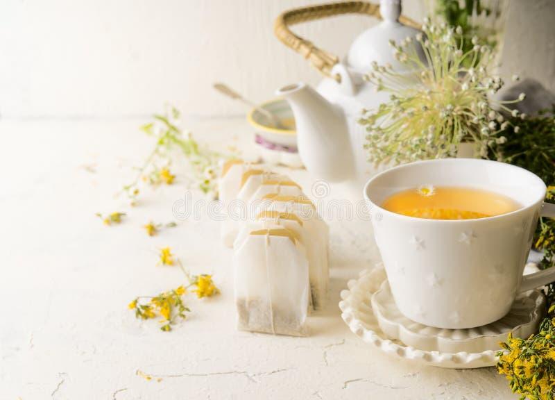 Tasse de thé blanche avec des sacs à thé de tisane se tenant sur la table blanche avec la théière et les herbes et les fleurs méd photographie stock