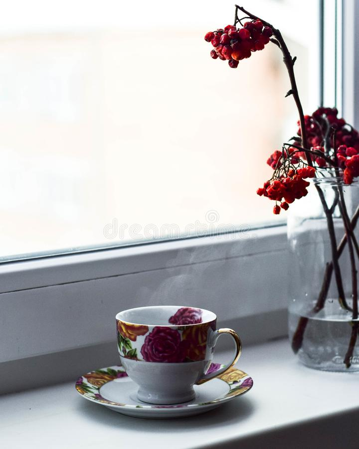 tasse de thé/de café sur le rebord de fenêtre avec la sorbe dans le verre image libre de droits