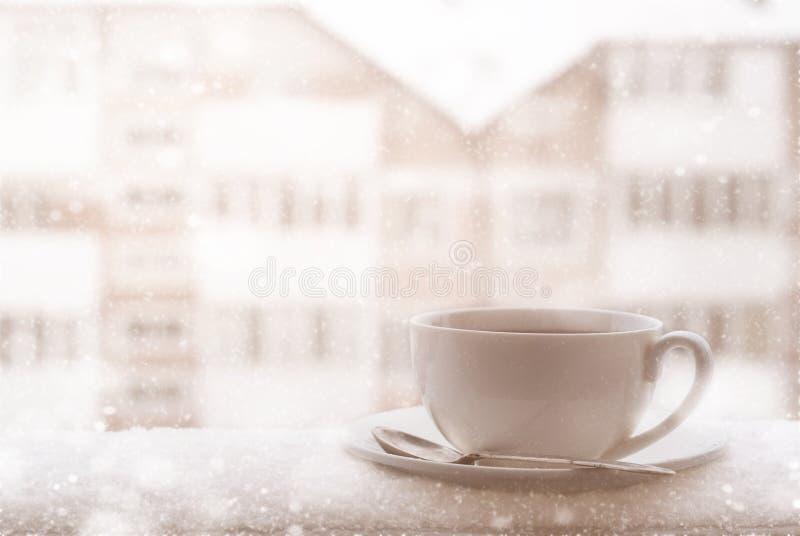 Tasse de thé chaud extérieure dans le jour de chute de neige photo libre de droits