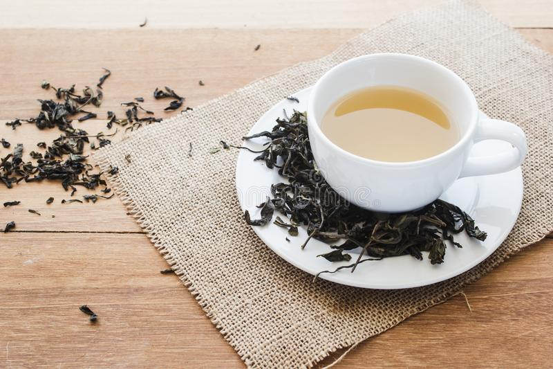 Tasse de thé chaud sur la toile à sac avec les feuilles de thé sèches sur la table en bois avec l'espace de copie photographie stock libre de droits
