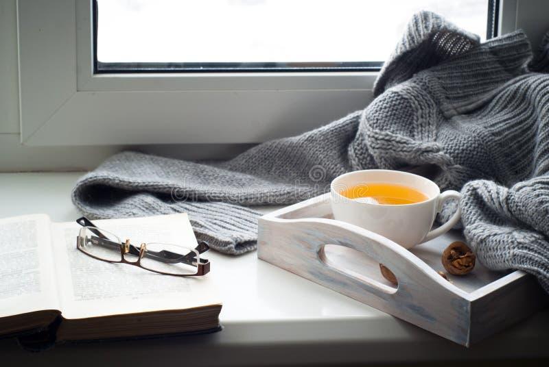 Tasse de thé chaud sur le rebord de fenêtre images libres de droits