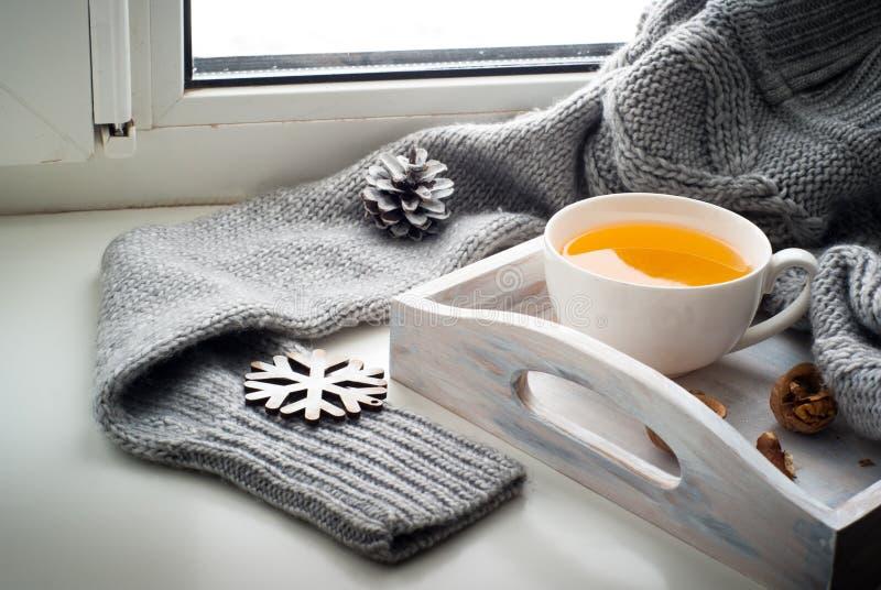 Tasse de thé chaud sur le rebord de fenêtre images stock