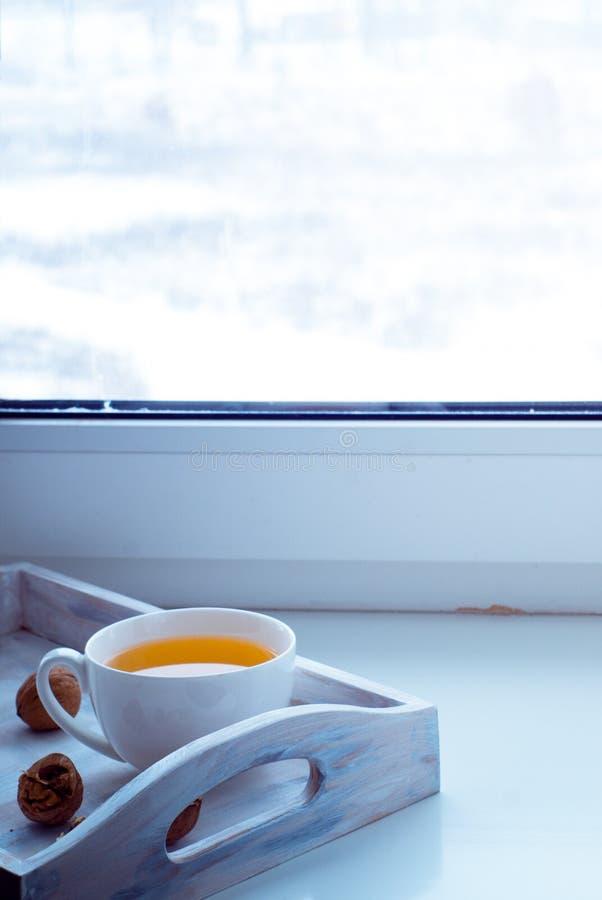 Tasse de thé chaud sur le rebord de fenêtre photo stock