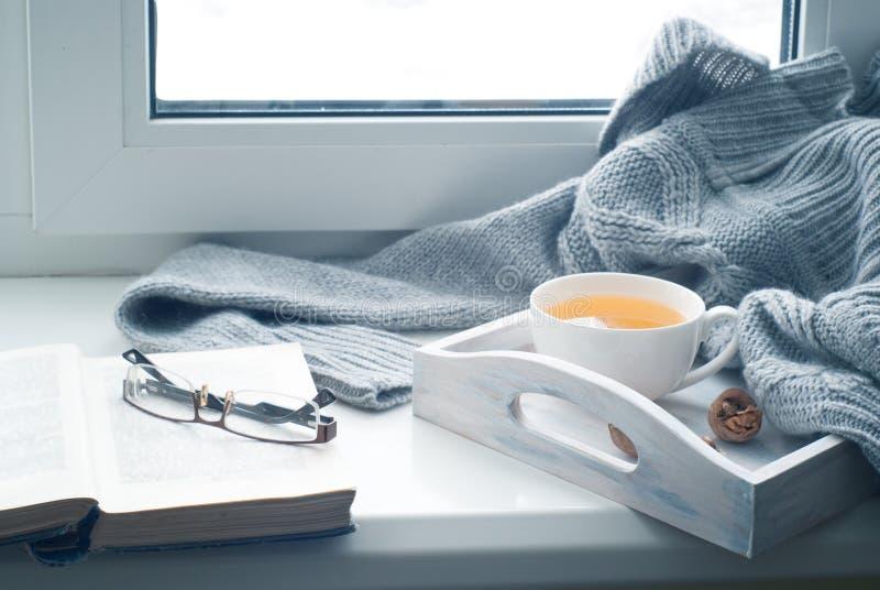 Tasse de thé chaud sur le rebord de fenêtre photos libres de droits
