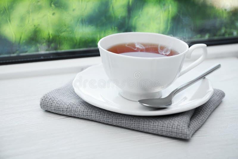 Tasse de thé chaud sur le rebord de fenêtre en bois blanc photographie stock