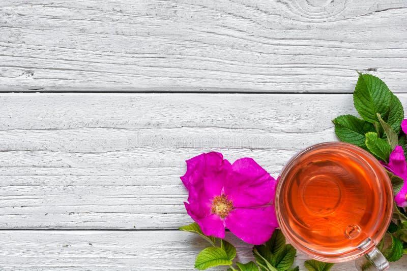Tasse de thé de fines herbes de hanche rose au-dessus du fond en bois blanc photographie stock libre de droits