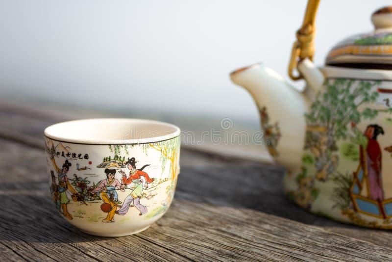Tasse de thé de style chinois avec la théière sur la table en bois photographie stock
