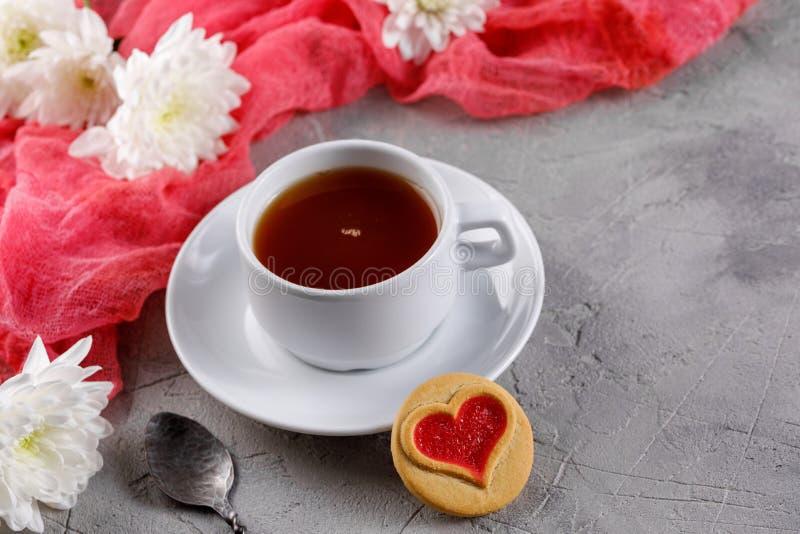 Tasse de thé et de biscuits avec des coeurs sur un fond gris La belle vie immobile avec une tasse de thé, l'humeur de la Saint-Va photographie stock libre de droits