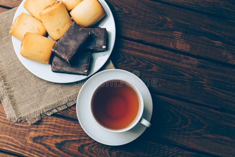 Tasse de thé et de biscuits avec une guimauve carrée en chocolat image stock