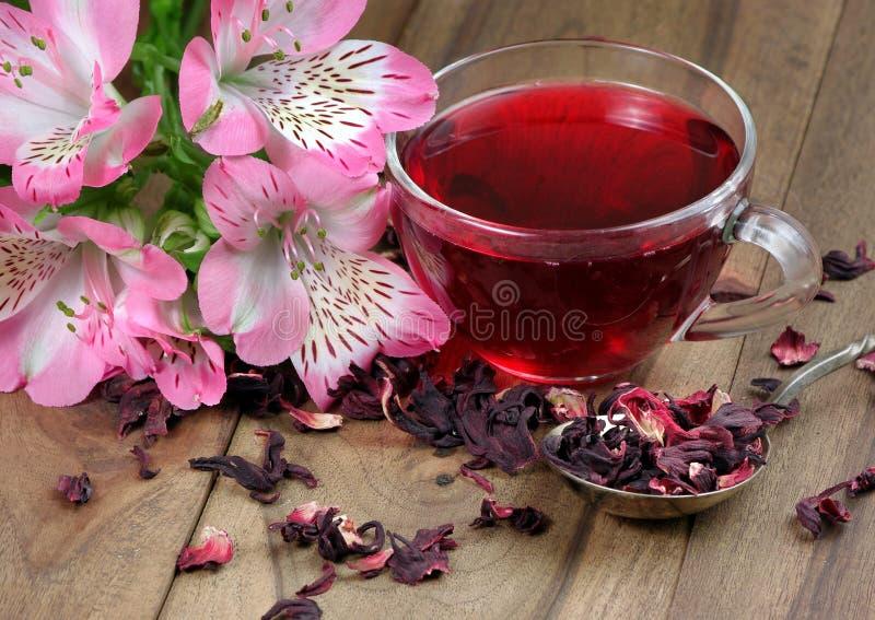 Tasse de thé de ketmie et un bouquet des fleurs de ressort sur une table en bois tisane pour le froid et la grippe image libre de droits