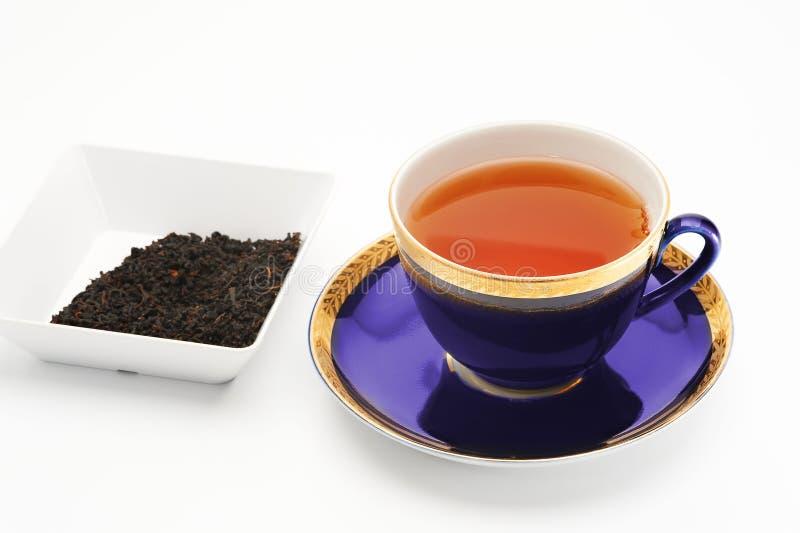 Tasse de thé noir et peu de cuvette avec des feuilles de thé photo stock