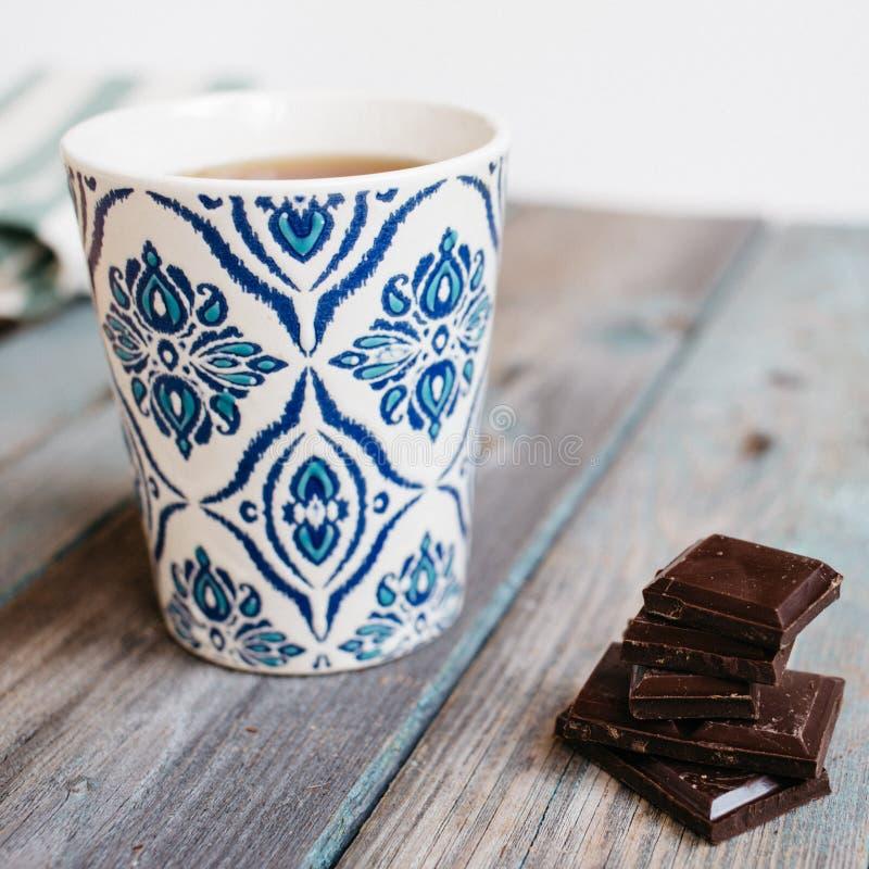 Tasse de thé ou café et chocolat sur une table en bois images libres de droits