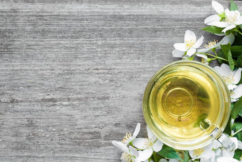 Tasse de thé vert avec le jasmin au-dessus du fond en bois rustique photographie stock libre de droits