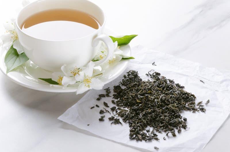 Tasse de thé vert chaud avec la saveur de jasmin, les fleurs fraîches de jasmin et le thé vert sec sur le papier, table de cuisin image stock