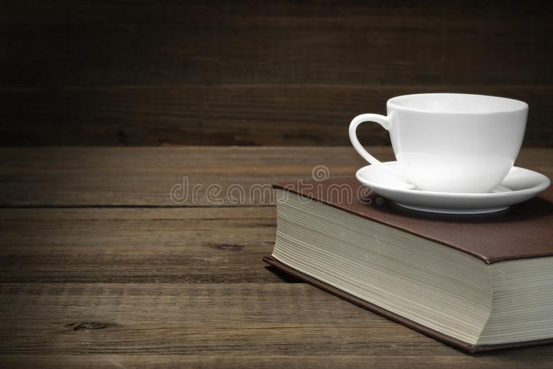 Tasse de thé vide sur le vieux livre rouge dans l'obscurité photographie stock libre de droits