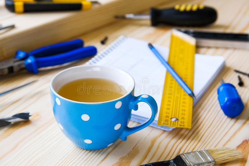 Tasse de th?, de dessins et d'outils de construction pour ?tablir une maison ou une r?novation d'appartement, sur une table en bo photos stock