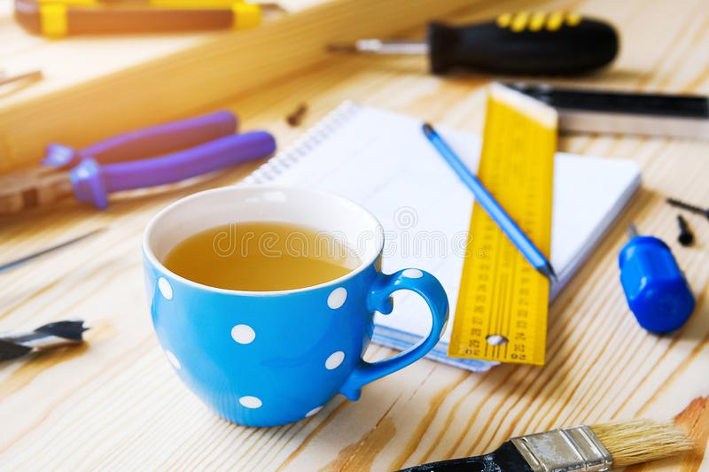 Tasse de th?, de dessins et d'outils de construction pour ?tablir une maison ou une r?novation d'appartement, sur une table en bo images stock