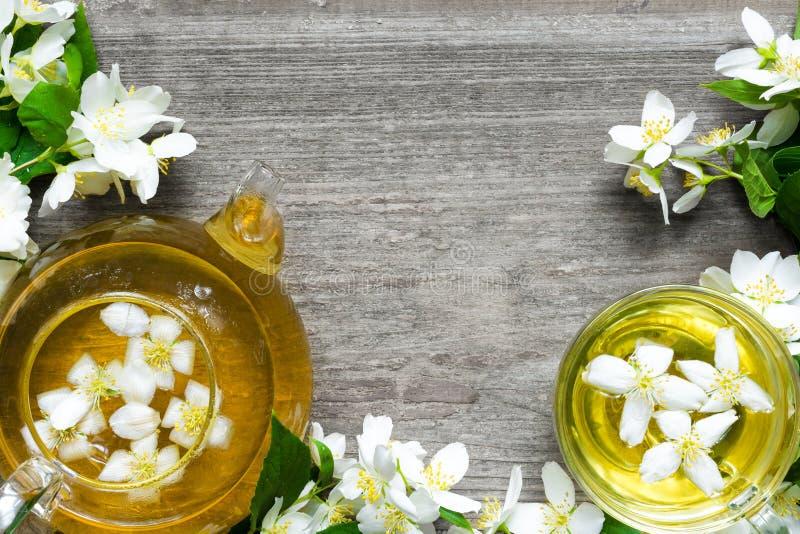 Tasse de tisane verte avec les fleurs et la théière de jasmin photo stock