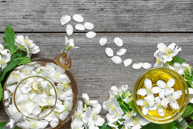 Tasse de tisane verte avec les fleurs et la théière de jasmin au-dessus du fond en bois rustique images libres de droits