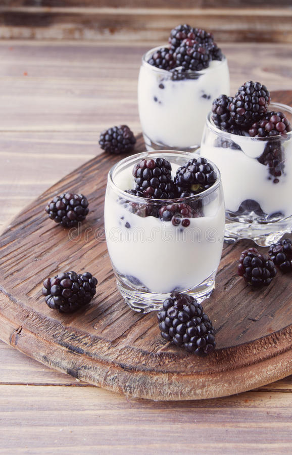 Tasse de yaourt avec la mûre sur la table en bois photo stock