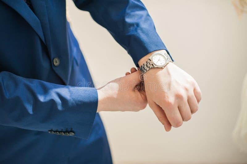 Tasse dello sposo l'uomo mette l'orologio fotografie stock libere da diritti