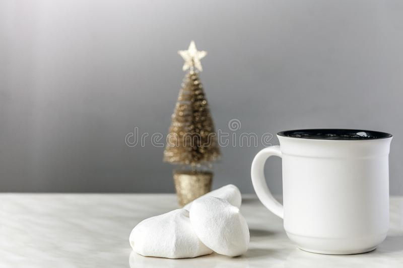 Tasse des meringues de thé et blanches et de l'arbre de Noël d'or photo stock
