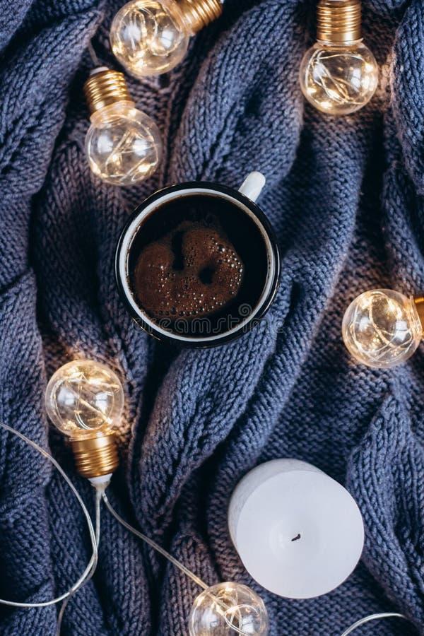 Tasse du café, de la bougie et du chandail de laine chaud, décorés des lumières menées image stock