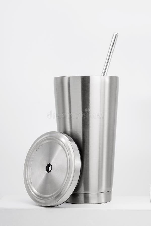 Tasse en acier sur l'étagère blanche Culbuteur inoxydable vide pour votre conception Bouteille isolée pour garder votre boisson photo libre de droits