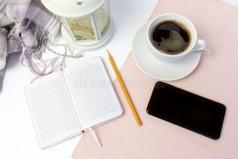 Tasse en céramique blanche de café, de carnet, de crayon, de décoration de vacances et de smartphone sur la table blanche, couver image stock