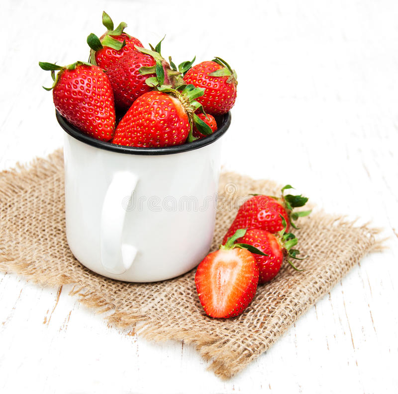 Tasse en métal avec des fraises photographie stock