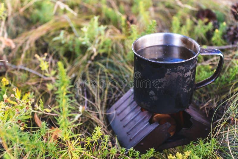 Tasse en métal avec le thé chauffant sur la cheminée dehors brûleur sec à alcool de brasero d'alcool photographie stock libre de droits