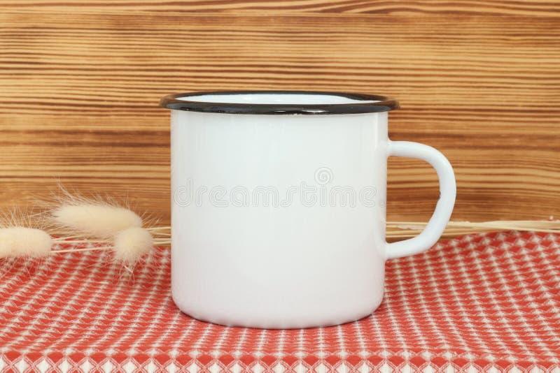 Tasse en métal blanc d'émail de feu de camp avec la ligne noire sur le bord Vieux calibre de conception de tasse de bidon images stock