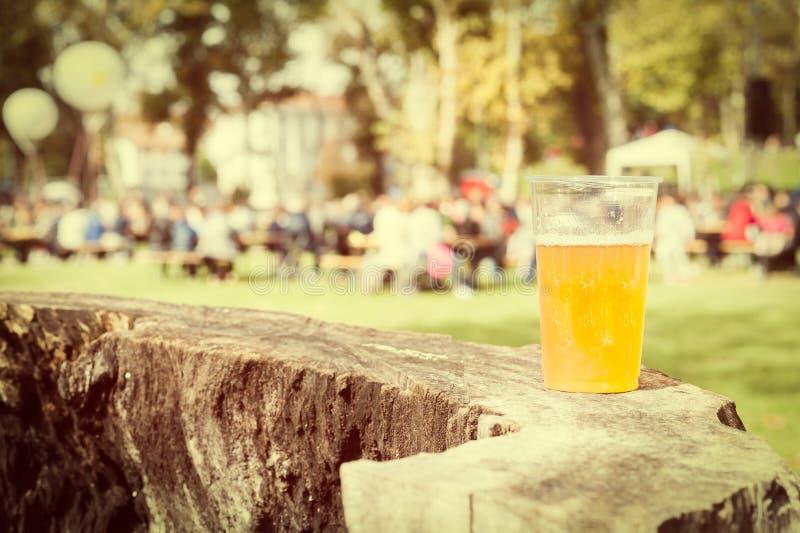 Tasse en plastique de bière sur un tronc d'arbre Photo de type de cru image libre de droits