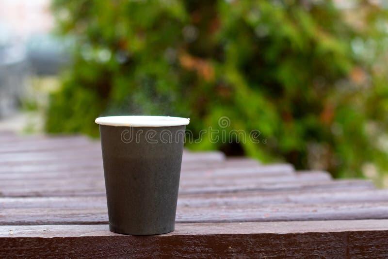 Tasse en plastique grise avec du café sur le fond des branches photos stock